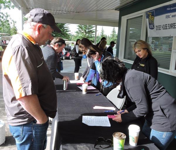 Registrants at the Odyssey Sunrise Golf Tournament Registration Table